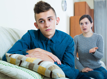 Serious mother lecturing unpleased teenager in home interior