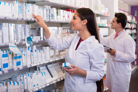 Photo pour Smiling pharmacist and indian pharmacy technician posing in drugstore - image libre de droit
