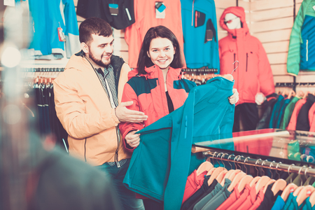Smiling positive couple examining track jackets in sports clothes store