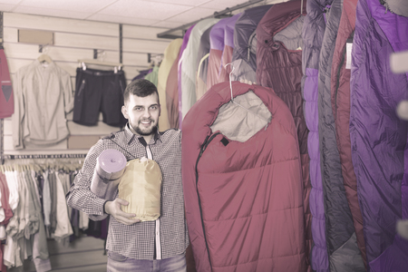 Young smiling cheerful  man choosing touristic equipment in sports equipment store