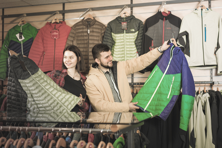 Young smiling couple choosing on windcheater in sports clothes store