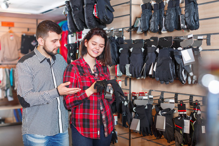 Young couple choosing protective gloves in a sports clothes store. Focus on both persons