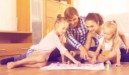 Foto de Happy young parents and two little daughters playing board game at home - Imagen libre de derechos