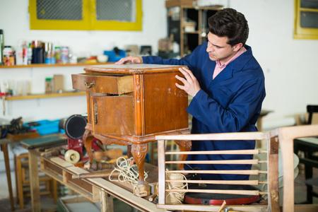 Foto de Man carpenter wearing blue overalls restoring furniture in restoration studio - Imagen libre de derechos