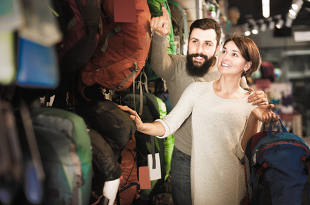 Young couple looking for interesting models of backpacks in the shop