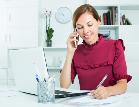 Photo for young attractive female employee answering on phone and taking notes at office - Royalty Free Image