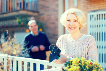 Photo pour Senior woman with gardening accessories on a terrace near her house with her husband holding a cup of coffee in a background - image libre de droit