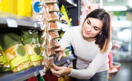 Foto de Young american woman choosing delicious snacks in supermarket - Imagen libre de derechos