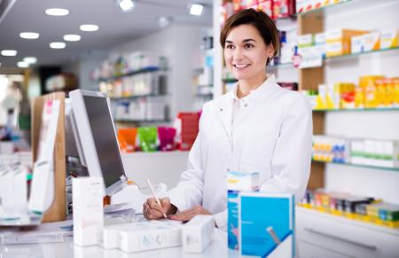 Foto de Smiling pharmacist ready to assist in choosing at counter in pharmacy - Imagen libre de derechos