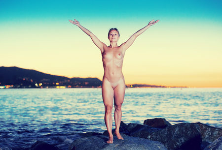 Photo pour Nude woman 24-31 years old is standing on a rock near the sea at the dawn. - image libre de droit
