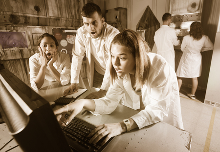 Photo for Company of young people solving different conundrum in quest room in view as abandoned lab - Royalty Free Image