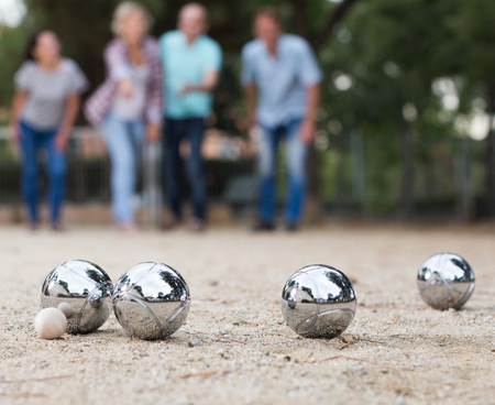Photo pour Males and females playing petanque in th park on holidays - image libre de droit