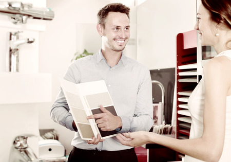 Photo pour Joyful assistant working with customer in kitchen furniture  store - image libre de droit