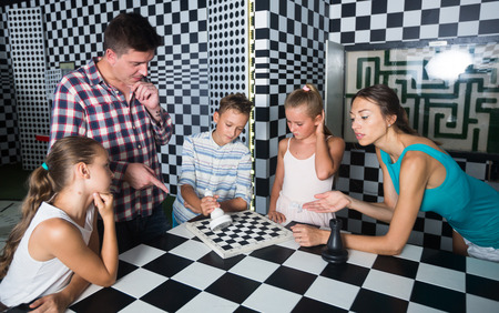 Photo for Young family is visiting of escape room stylized under chessboard. - Royalty Free Image