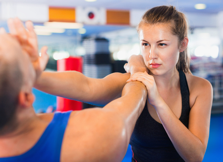 Foto de Strong bold  woman is training with man on the self-defense course in gym. - Imagen libre de derechos