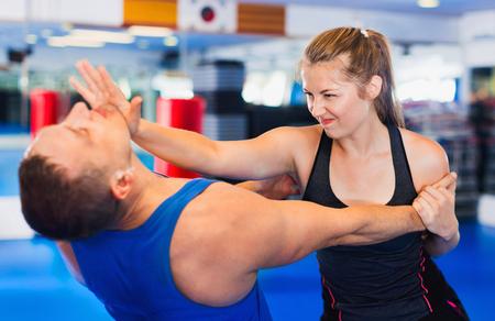 Foto de Bold positive  woman is training with man on the self-defense course in gym. - Imagen libre de derechos