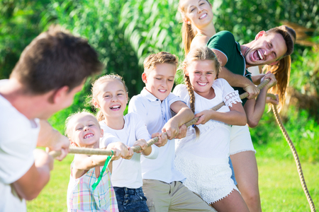 Photo pour Group of laughing young people with kids having fun together outdoors pulling rope - image libre de droit