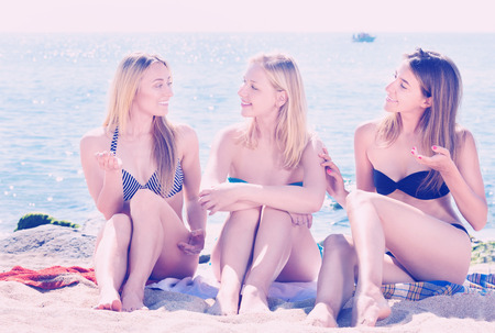 Photo for Portrait of three cheerful young women in swimsuits chatting on a beach. Focus on all persons - Royalty Free Image
