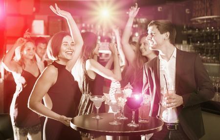 Foto de Positive glad colleagues dancing on corporate party with cocktails in hands - Imagen libre de derechos