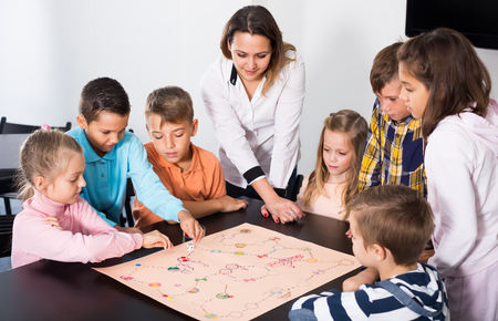 Foto de Woman and happy children sitting at table with board game and dice in school - Imagen libre de derechos