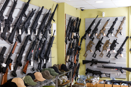 Photo pour Guns hangs on the wall in military store closeup - image libre de droit