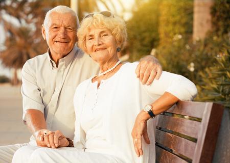 Foto de cheerful pensioners woman and man sitting and hugging outdoors - Imagen libre de derechos