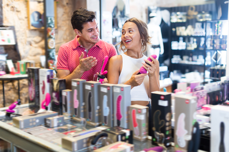 Photo pour Portrait of happy girl and man consumers holding sexy toys in the sex shop - image libre de droit