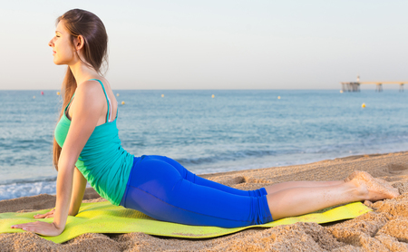 Photo pour Smiling young woman in blue T-shirt is practicing stretching on the beach. - image libre de droit
