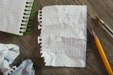 Foto de Torn crumpled notebook sheet in cage surrounded by stationery - Imagen libre de derechos