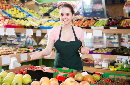 Photo pour Friendly attractive italian salesgirl proposing fresh fruits and vegetables in supermarket  - image libre de droit