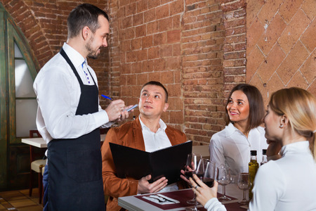 Foto de Male waiter taking order from visitors in country restaurant - Imagen libre de derechos