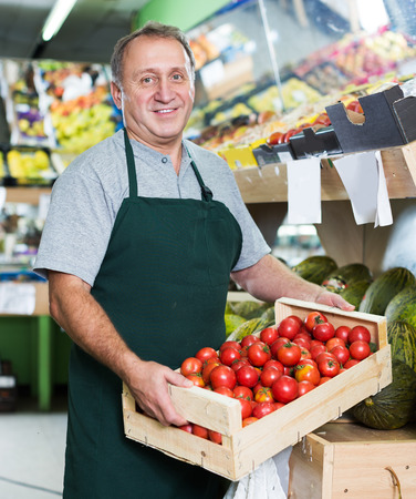 Photo pour adult seller is offering red tomatos in the market. - image libre de droit