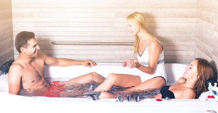 Photo for Three friends are resting in jacuzzi with petals in spa salon. - Royalty Free Image