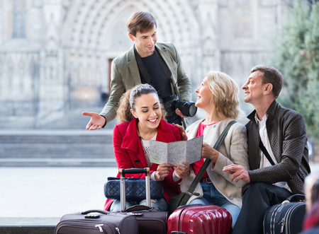 Foto de Positive family of four with luggage checking direction in map outdoor - Imagen libre de derechos
