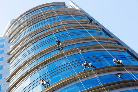 Foto de Group of industrial alpinists working on large windows of skyscraper - Imagen libre de derechos