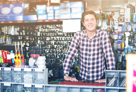 Photo pour Smiling adult man standing near the counter and selling keys in hardware shop - image libre de droit