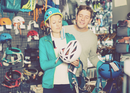 Girl and the guy choosing at a shop of sports equipment the mountaineering equipment. Focus on man