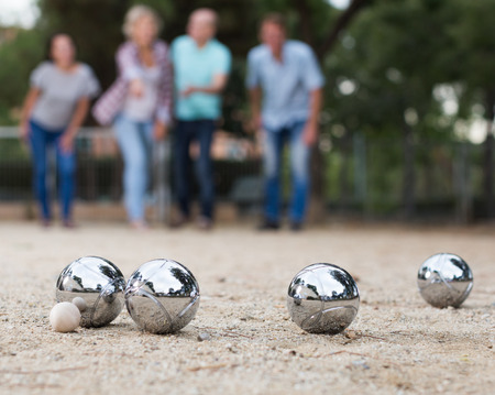 Photo pour Portrait of friendly people playing petanque at leisure - image libre de droit