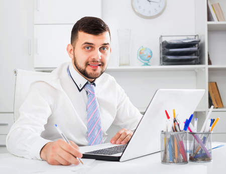 Photo pour Young happy cheerful positive male worker working productively on project in office - image libre de droit