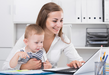 Photo pour Satisfied mother with kid is productively working behind laptop in office. - image libre de droit