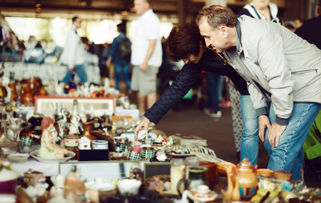 Photo pour Elderly man and woman choosing interesting souvenirs at traditional flea market - image libre de droit