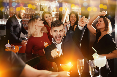 Photo pour Cheerful guy expressively dancing partying in bar - image libre de droit