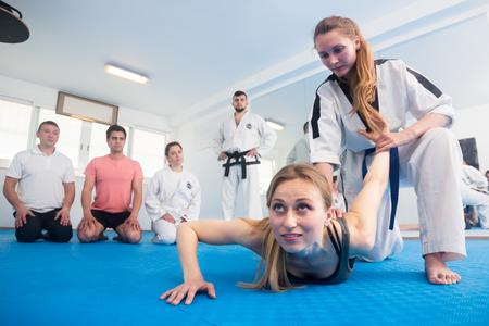 Photo pour Young girl in a taekwondo training teaches new tricks of defense - image libre de droit
