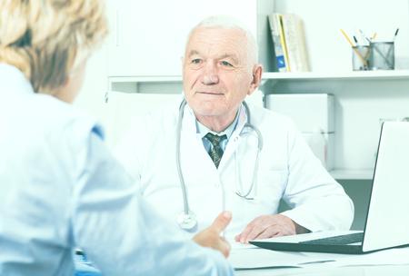 Foto de Old female visitor consulting smiling aged man doctor in hospital - Imagen libre de derechos