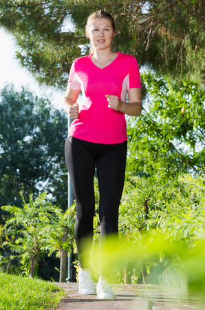 Photo pour Smiling woman in pink T-shirt is running around in the park. - image libre de droit