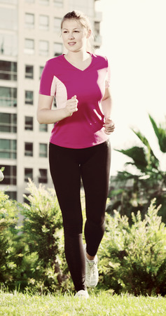 Photo pour Adult female in pink T-shirt is running around the urban. - image libre de droit