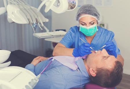 Foto de woman dentist in uniform health tooth visitor in dentist's room - Imagen libre de derechos