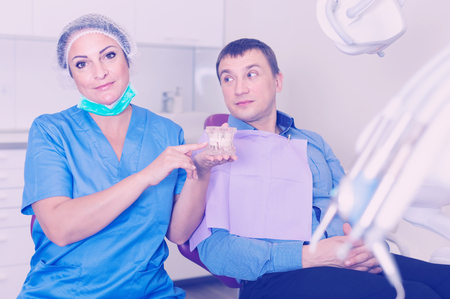 Foto de professional positive doctor woman and patient sitting in medical chair - Imagen libre de derechos