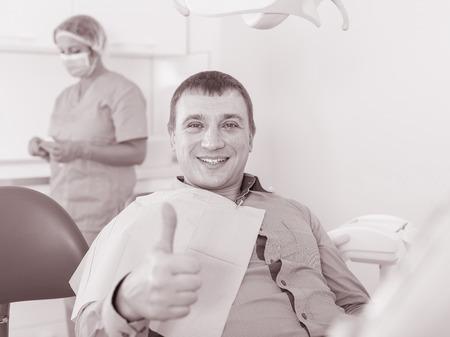 Foto de portrait of male visitor sitting and smiling in dentist's office - Imagen libre de derechos