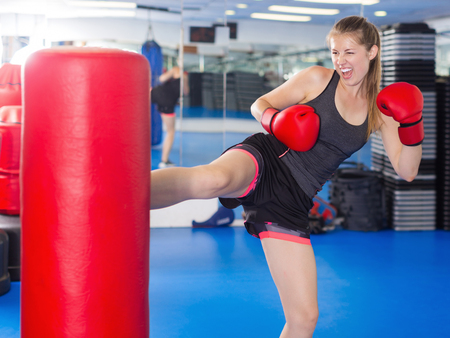 Foto de Portrait of active woman practicing with punching bag in box gym - Imagen libre de derechos